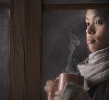 woman by the window cozy while cold